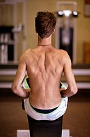 the back of a man rowing at a gym
