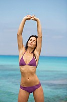 Portrait of a brunette woman stretching at the beach, Formentera, Balearic Islands