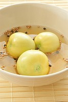 fresh green organic tomatoes in vinegar with spices