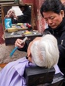 Street front barber at work in Hanoi, Vietnam