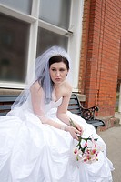 A young woman in a bridal gown, crying and sitting on a bench by city hall in Rosalia, Washington, USA.