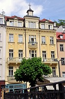 Old hotel with green tree in front, Karlovy Vary ,Czech Republic