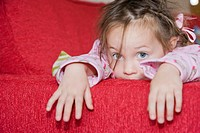 4 years old girl in pink pyjama lying on red sofa bed.