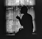 Silhouette of a stylish women smoking in 1926. During the 1920s, many women took up cigarette smoking, which was a symbol of women's independence befo...