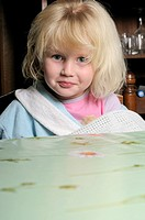 Stock photo of a portrait of a young child sitting at a table
