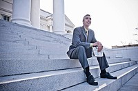 Caucasian businessman sitting on steps with newspaper