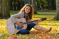 Hispanic woman playing guitar in park