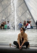 A lonely woman sits and relaxes in Louvren, Paris