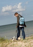 A man walking his dogs at beach in the fall