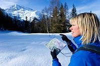Women orienteering in snowy mountains