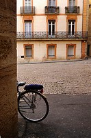 A bicycle left leaning against a wall in Pezenas, France