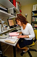 A 50_year_old self_employed woman works in her home office in Mission Viejo, California. The small office home office has gone through a great transfo...