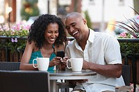 Couple at cafe looking at cell phone together