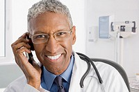 Smiling mixed race doctor talking on cell phone