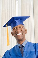 Mixed race man in graduation cap and gown