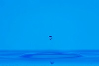blue droplet hitting the water surface splashing it up