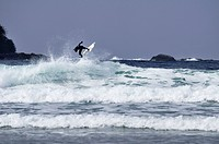 Surfer getting air on the crest of a wave at Chesterman Beach, Tofino, British Columbia, Canada.