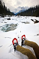 Person wearing snowshoes sitting on the snow covered banks of the Mistaya River during winter with Mount Sarbach 3155 metres/10351 feet in background,...