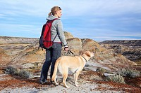 Woman hiking with her dog, standing on a scenic overlook. Horse Thief Canyon, Drumheller, Alberta, Canada.