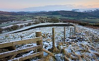 Snow dusted fence and fields looking towards Bwlch and snowy mountains beyond, Brecon Beacons National Park, Powys, Wales, United Kingdom, Europe