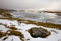 Melting snow on the moorland above an ice covered Llyn y Fan Fawr in winter, Black Mountain, Brecon Beacons National Park, Wales, United Kingdom, Euro...