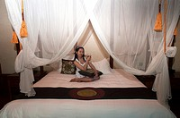 Thai beauty relaxing at the luxurious Dhara Dhevi Resort in Chiang Mai, Thailand