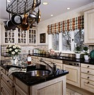Kitchen with light blond wood cabinets and counters, island area, hanging pot rack, sink area, potted plants by window