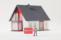 A miniature real estate agent figurine standing next to a VERKAUFT sold in German sign