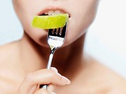 A woman biting into a piece of kiwi on a fork, close_up of mouth