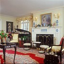 LIVING ROOMS _ Formal living room, Louis XV style chairs, grand piano, antiques, white fireplace mantel with wedgewood insets, Oriental rug, yellow wa...