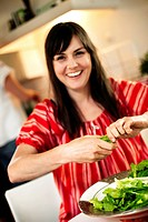 Dark_haired woman making a salad, Sweden.