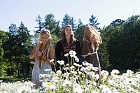 Three young women picking flowers in meadow