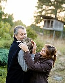 Mature couple embracing cat outdoors