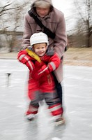 Father holding son on ice rink