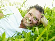 Ekero, Young man lying on grass, looking away and smiling
