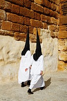 Hooded penitents near church during Semana Santa in Carmona near Seville, Andalusia, Spain