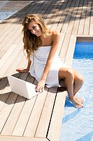 Blonde woman with laptop by the pool