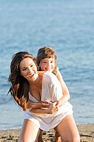 Daughter giving a hug to her mother in the seashore at the beach