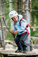 Little boy climbing in adventure park