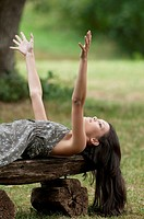 Beautiful young woman enjoying nature, lying on a wood bench  Taken in Lipica, Slovenia  Concept: teenagers and nature