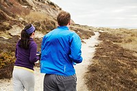 Couple running along coastal path