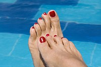 lady's feet by a swimming pool