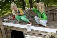 Girls painting wooden structure