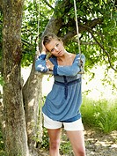 Young woman leaning on swing