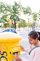 Woman posting postcard to postbox