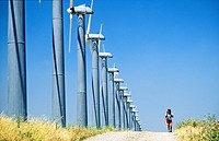 Wind turbines, part of the massive wind farm complex at Altamont near Livermore, California, USA  Woman walking on track
