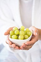 Man holding bowl of grapes, close_up
