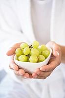Man holding bowl of grapes, close_up