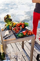 Man standing by table full of vegetables on jetty