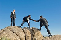 Businessman helping co_worker onto rock